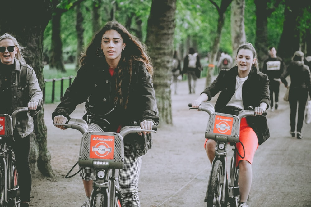 three women riding bicycles on parked