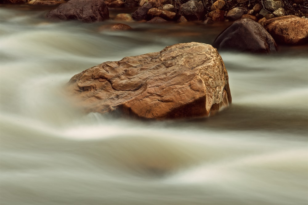 brown rock on body of water
