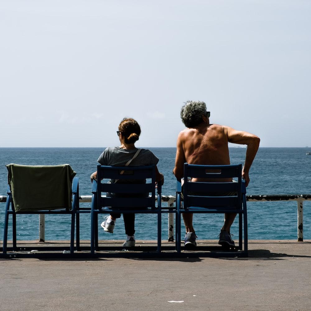 man and woman siting facing sea