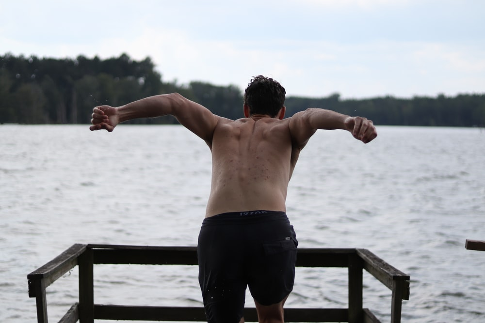 shallow focus photo of man in black shorts in front of body of water