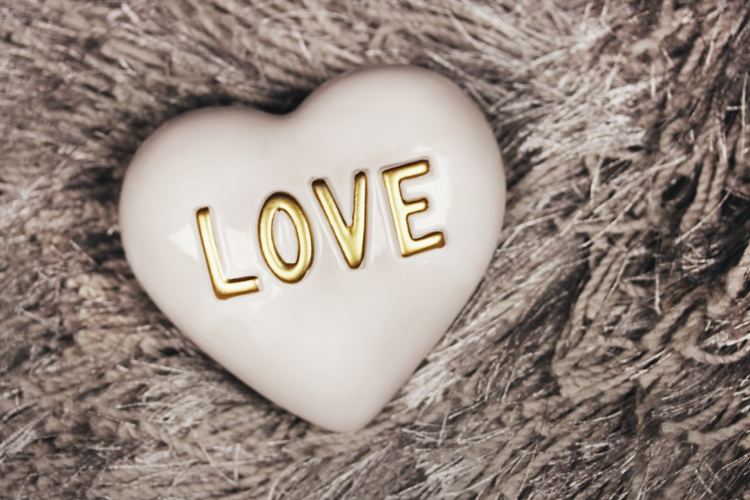 White ceramic heart with gold letters spelling out the message LOVE sits on a furry gray rug