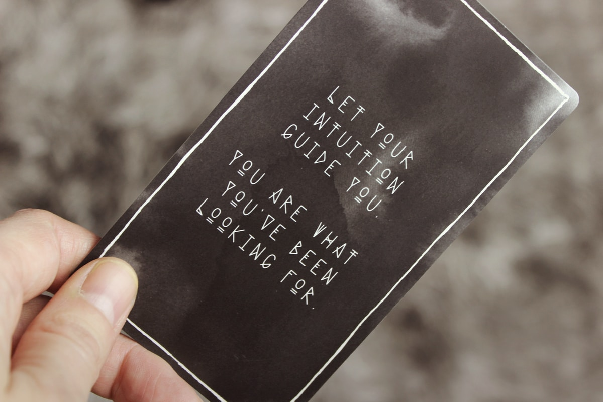 """A hand holding a black card with a thin white border.  The card says in white lettering, """"Let your intuition guide you. You are what you've been looking for."""""""