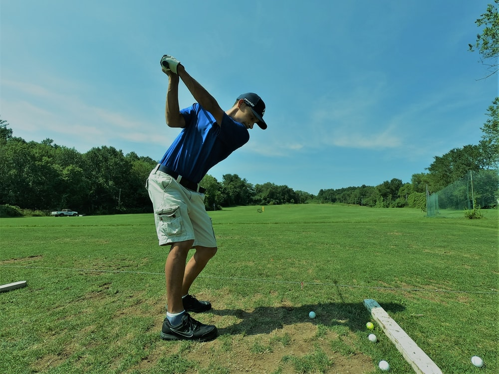 man in blue polo shirt playing golf
