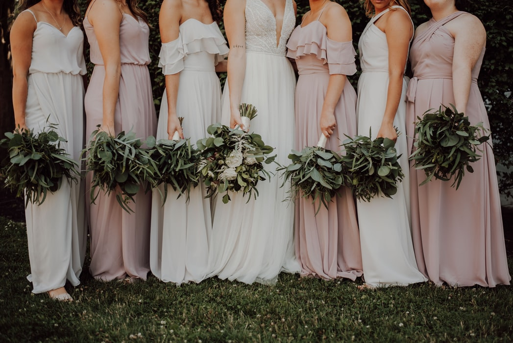 bride and her bridesmaid holding their wedding bouquet made up of different leaves