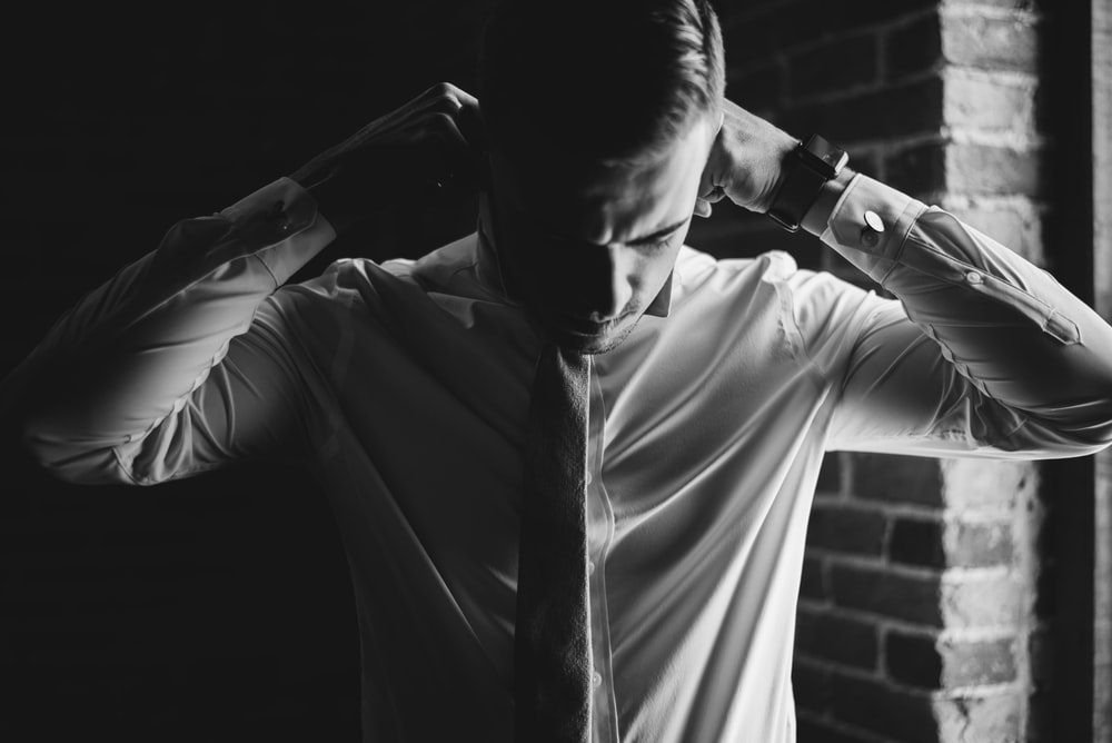 grayscale photo of man dressing up