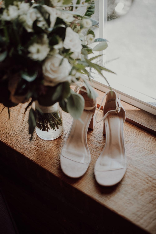 white open-toe ankle-strap heels beside flower vase