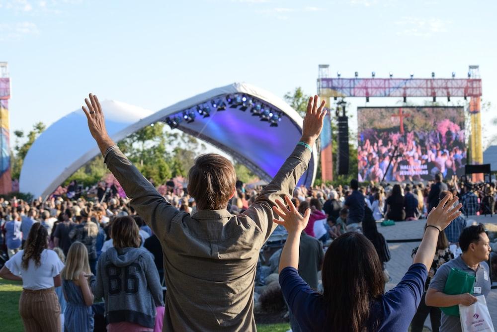 person wearing brown dress shirt raising both hands during concert