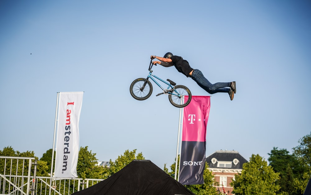 man riding on BMX bike under clear blue sky