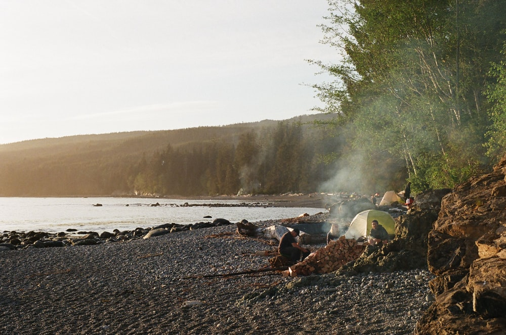 people camping on shore during golden hour