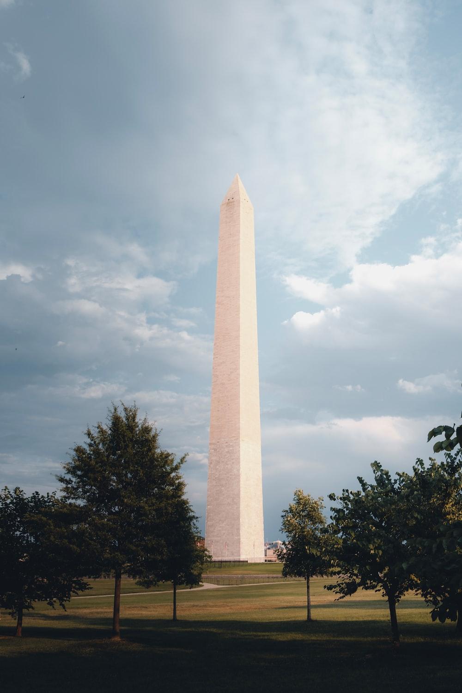 white obelisk near green trees