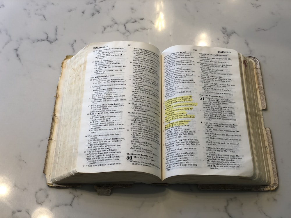 opened bible on white surface