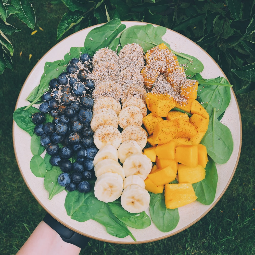 sliced blueberries, banana, and pineapple fruits in plate