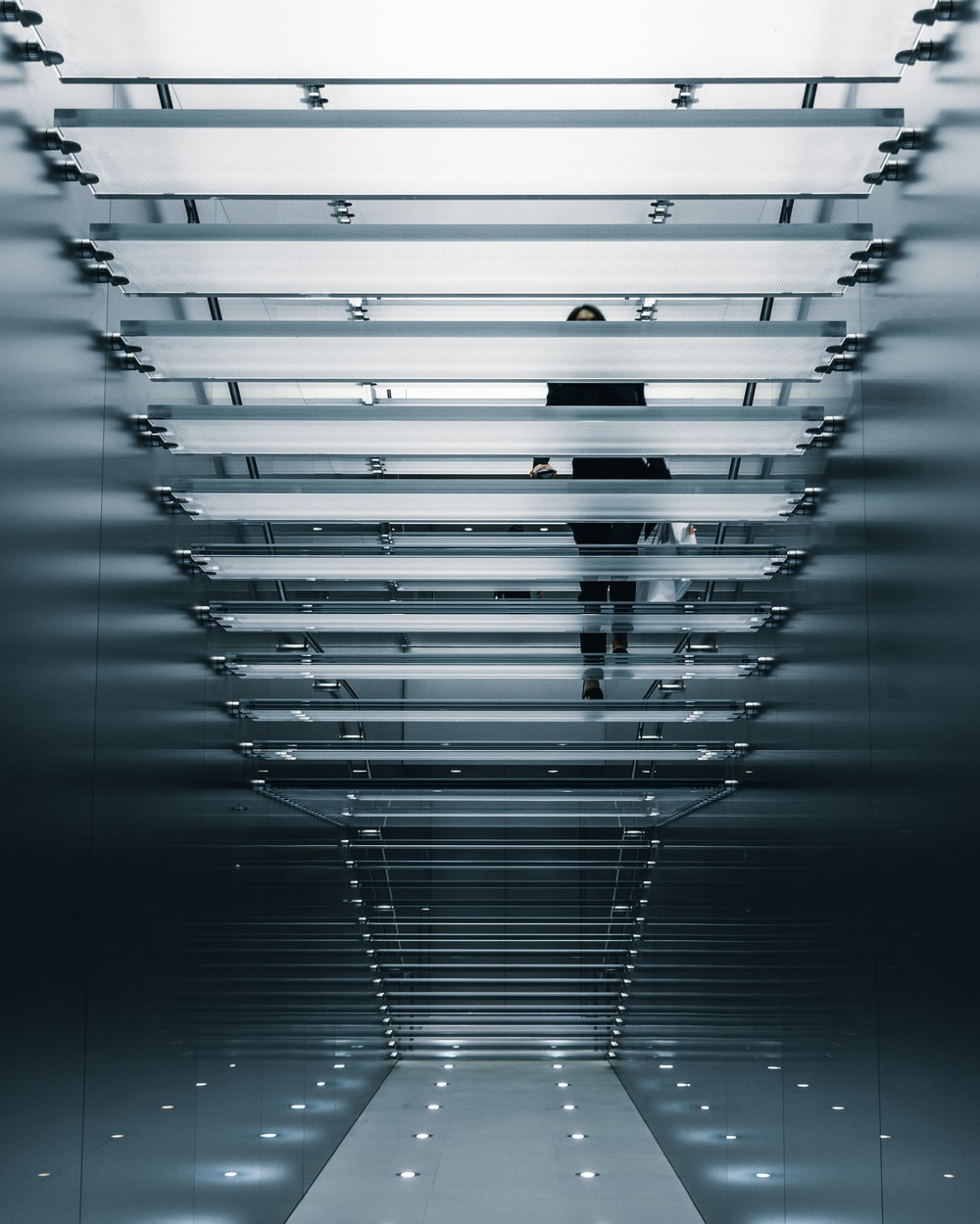 person on glass stair photo