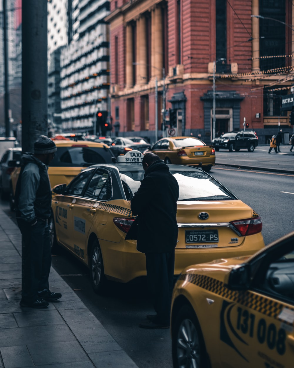 person wearing black trench coat standing on yellow cab