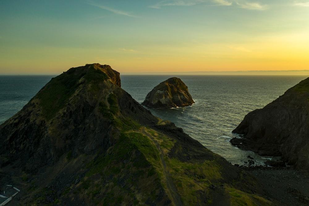 green rock mountain during sunset