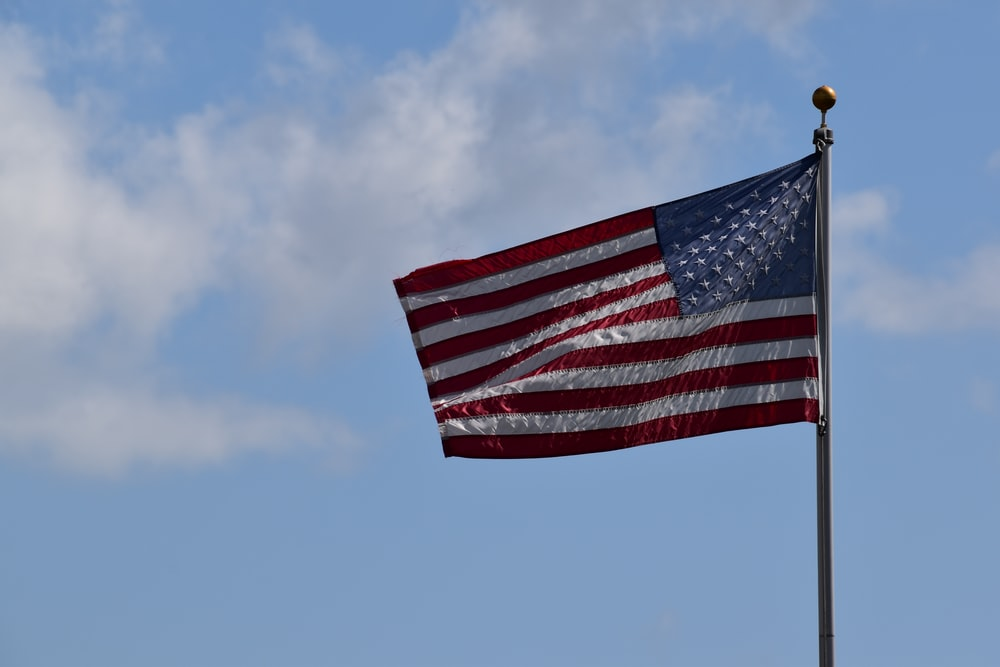 red, white, and blue USA flag in pole