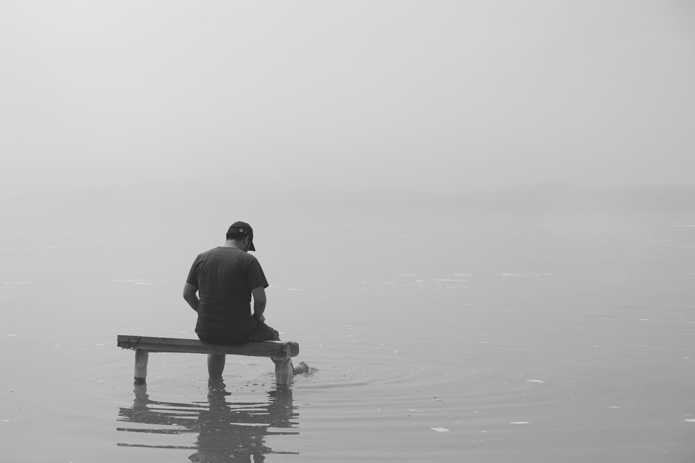 grayscale photo of man sitting on dock