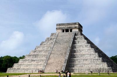 people near gray building mayan pyramid teams background