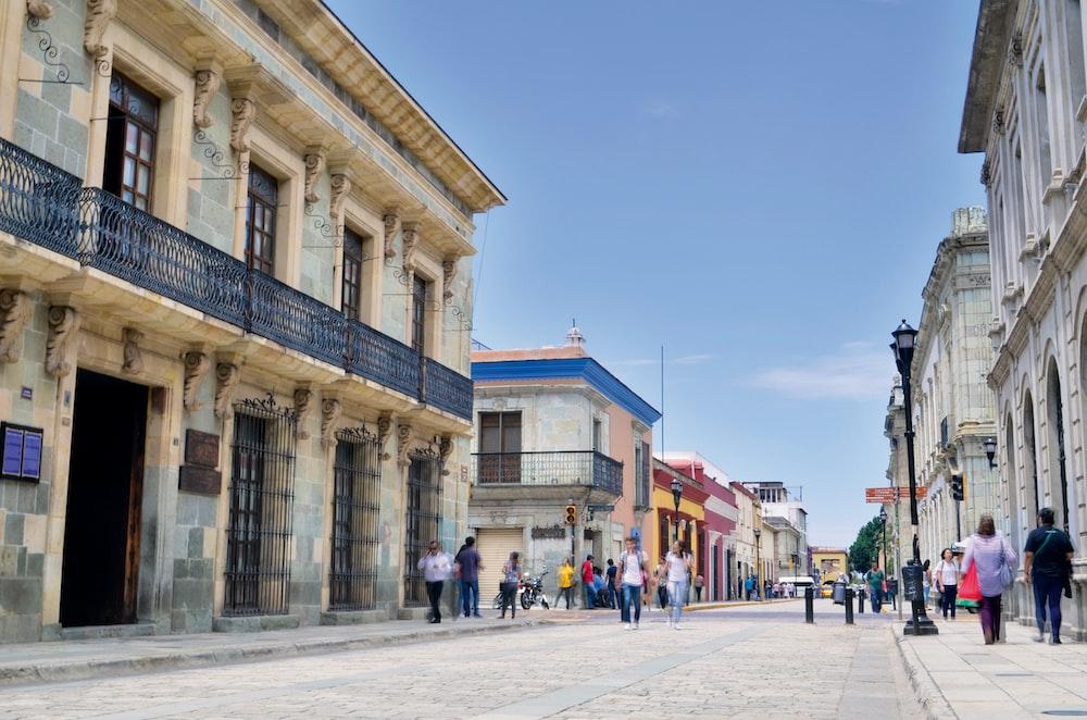 people walking on street under clear blue sky