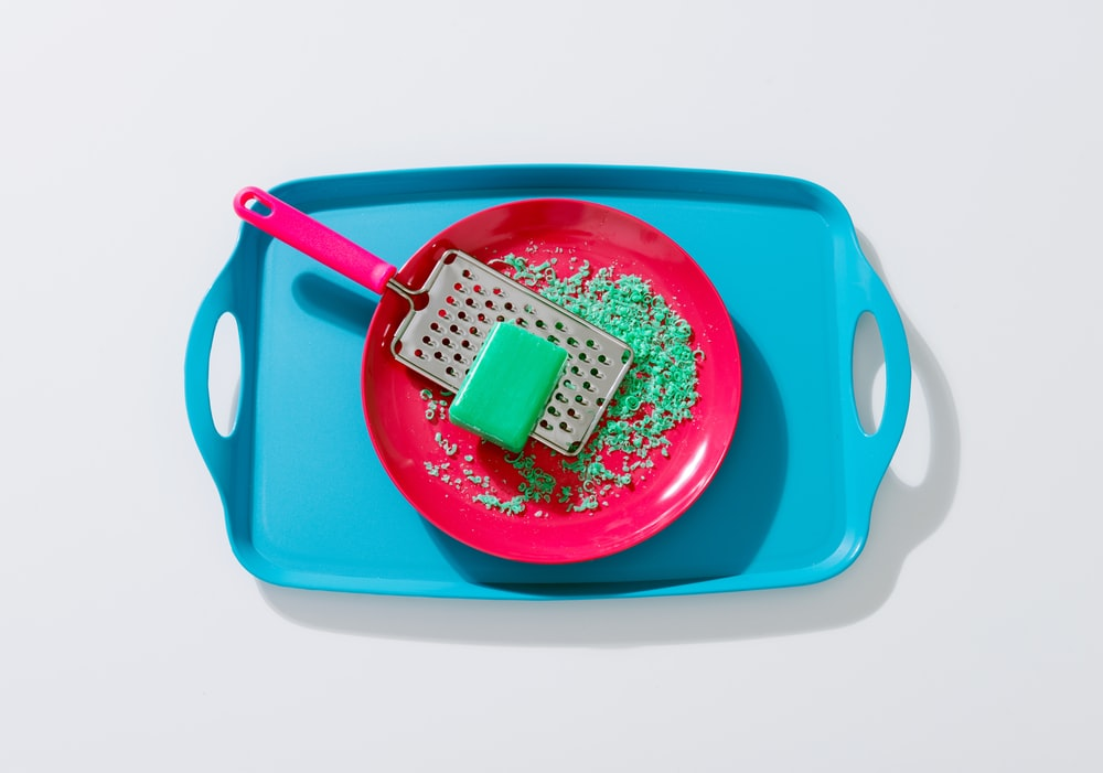 green soap on grey metal grater in round red ceramic plate
