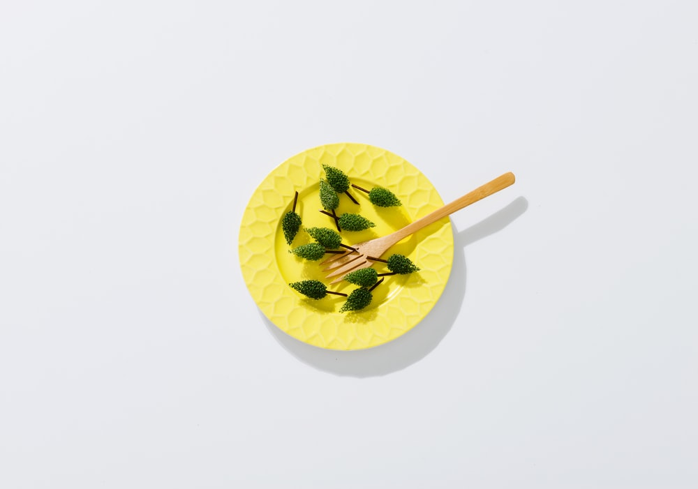 brown wooden fork on round yellow plate