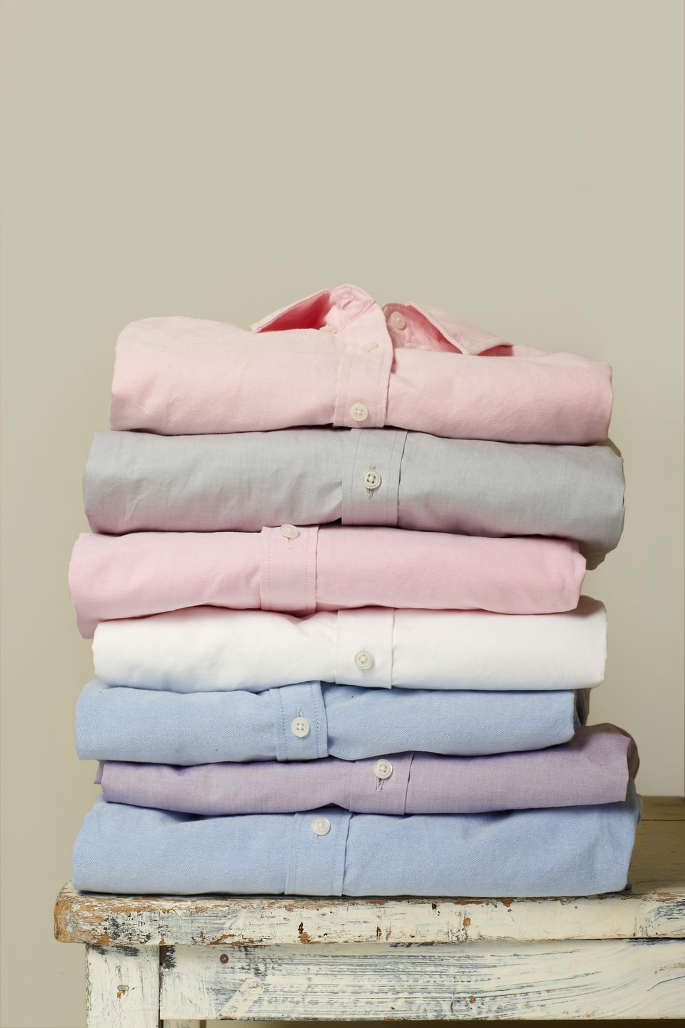 folded assorted-color collared button-up shirts on white wooden table