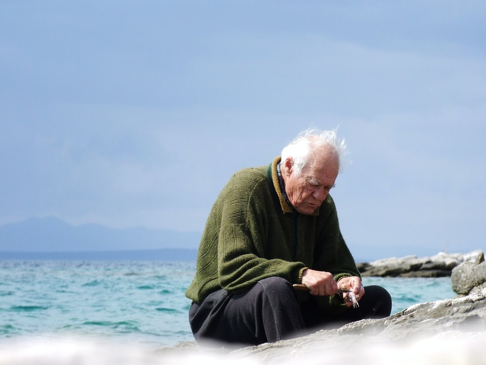 shallow focus photo of man in green long-sleeved shirt sitting near body of water