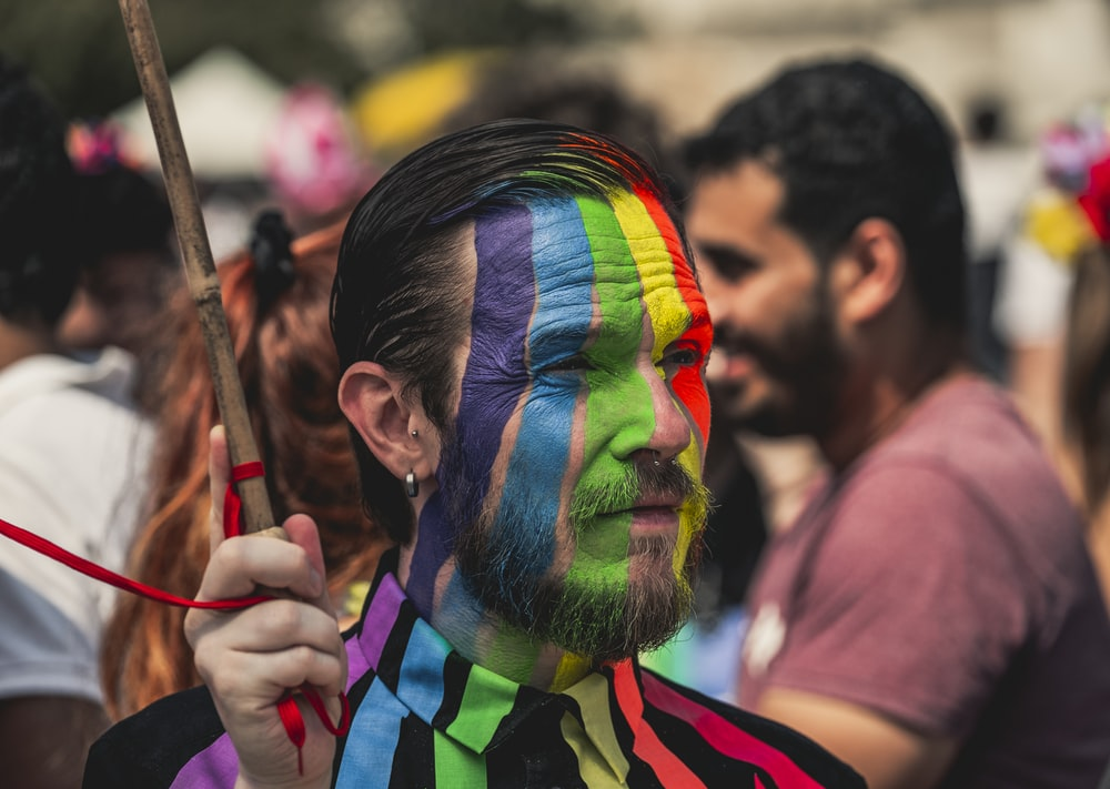 man wearing multicolored face paint