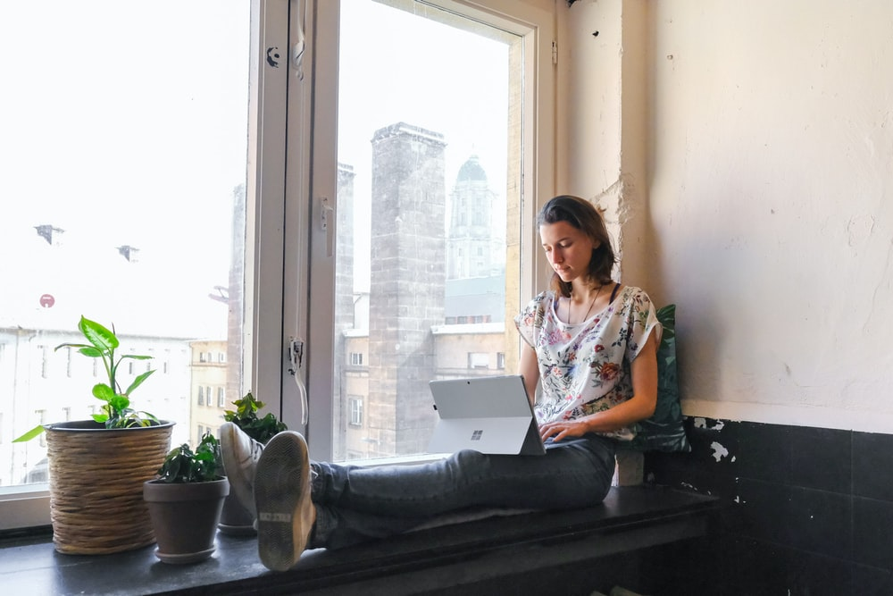 woman wearing white and red floral top sitting besides window