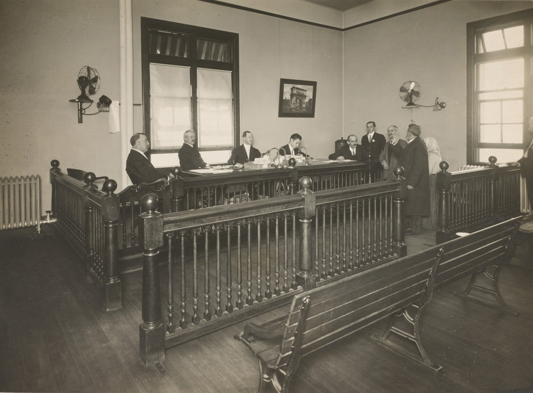 A bearded immigrant appearing before a board of inquiry, Ellis Island.