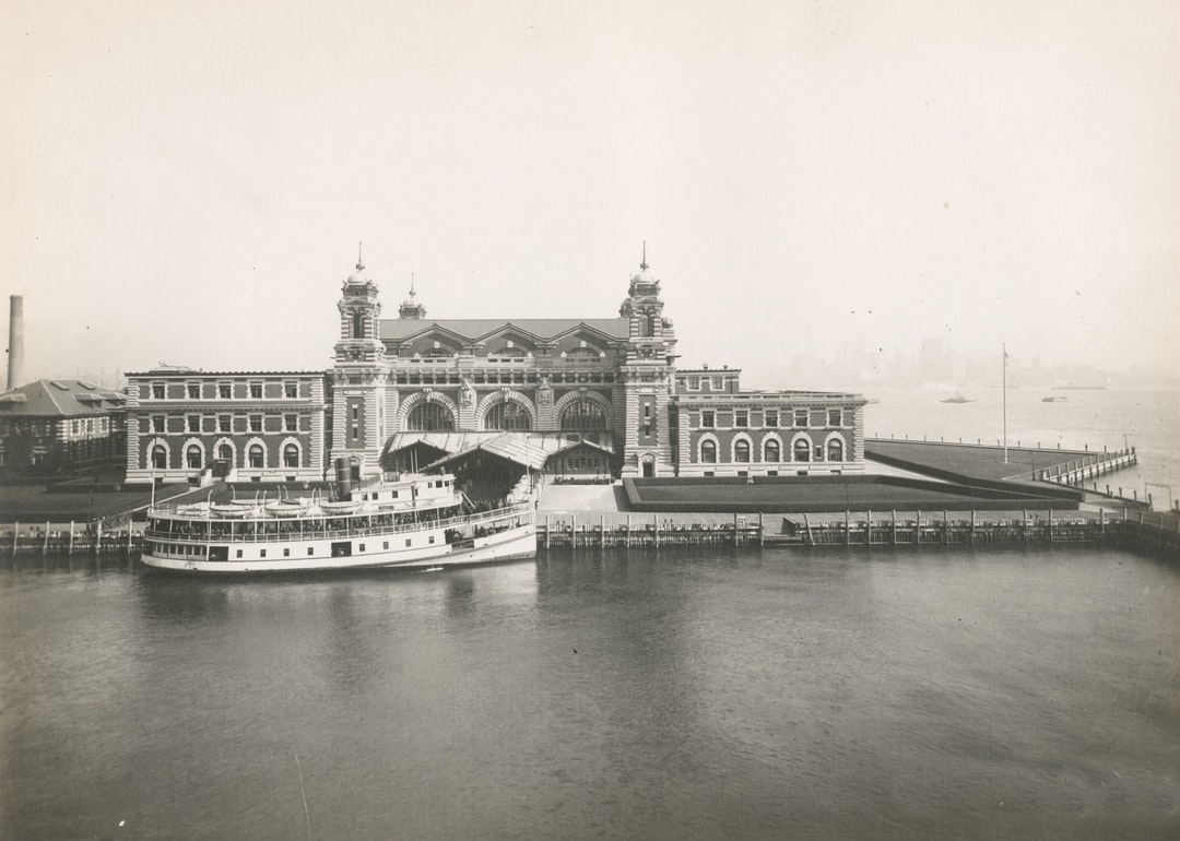 An excellent view of the front facade of the Immigration Station; a boat is docked in front. Ellis Island.