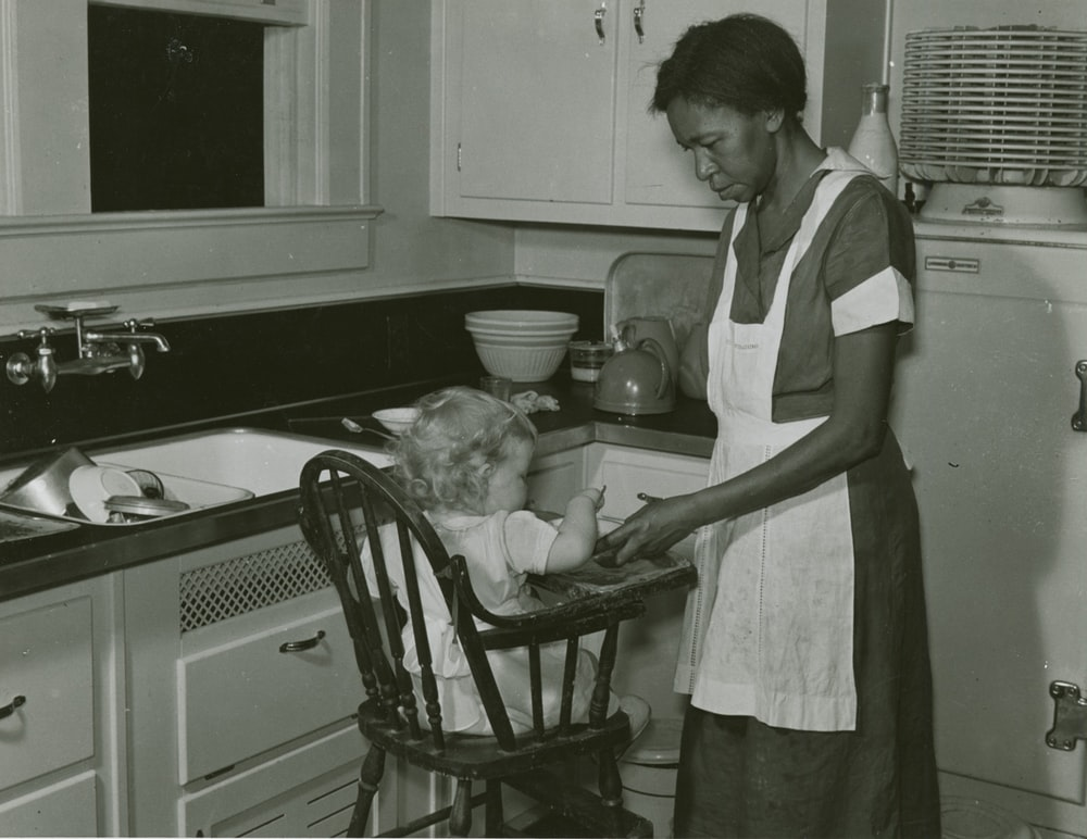 grayscale photography of woman standing in front of baby in highchair