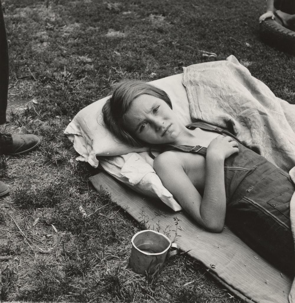 grayscale photography of girl lying near field