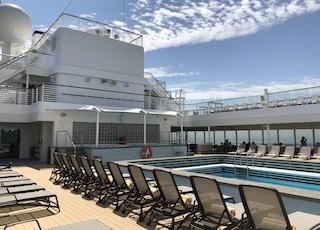 brown lounge chairs near big swimming pool