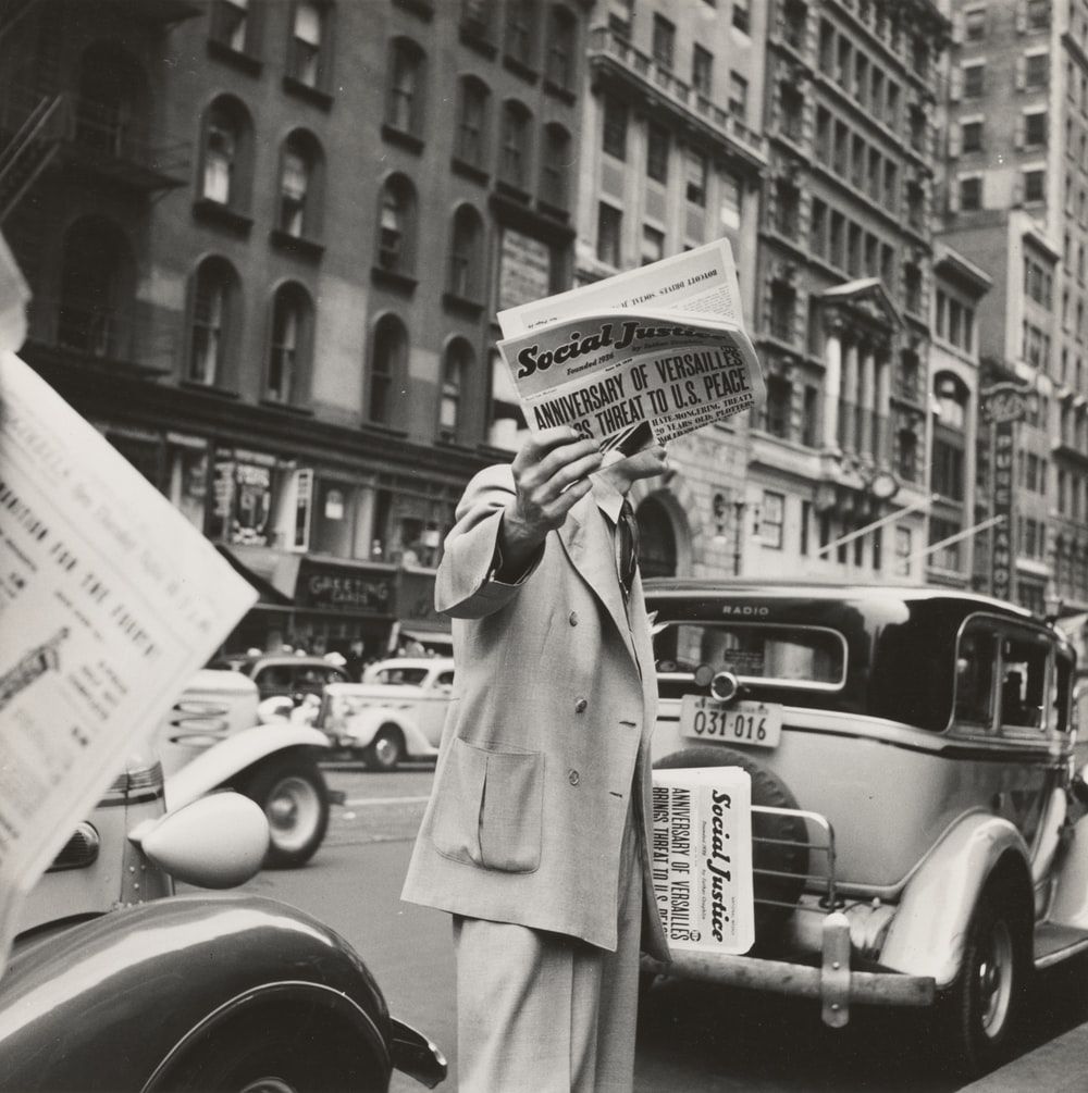 grayscale photography unknown person holding newspaper