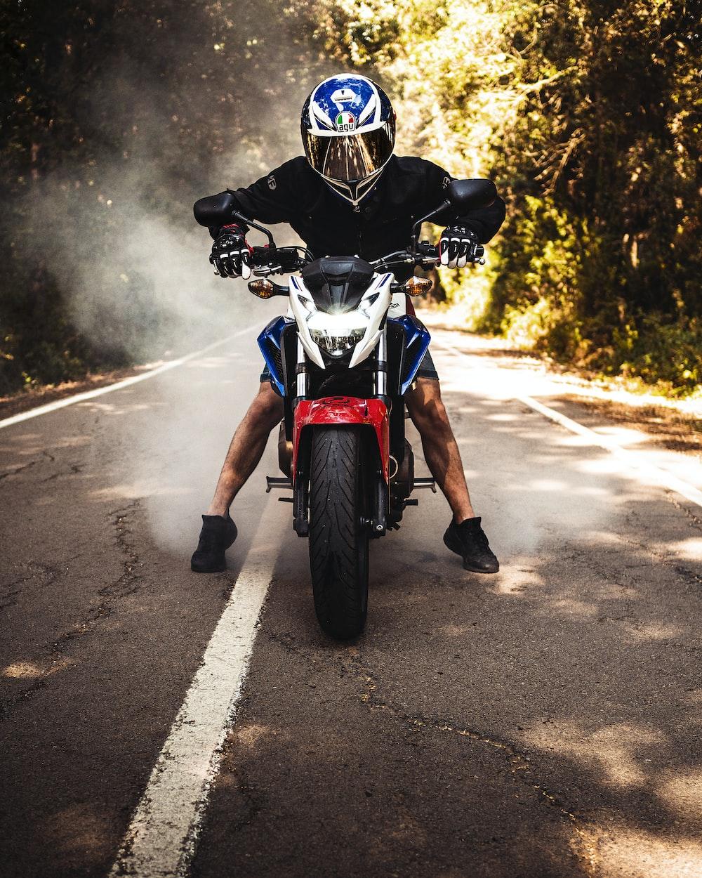 man riding on motorcycle near tree