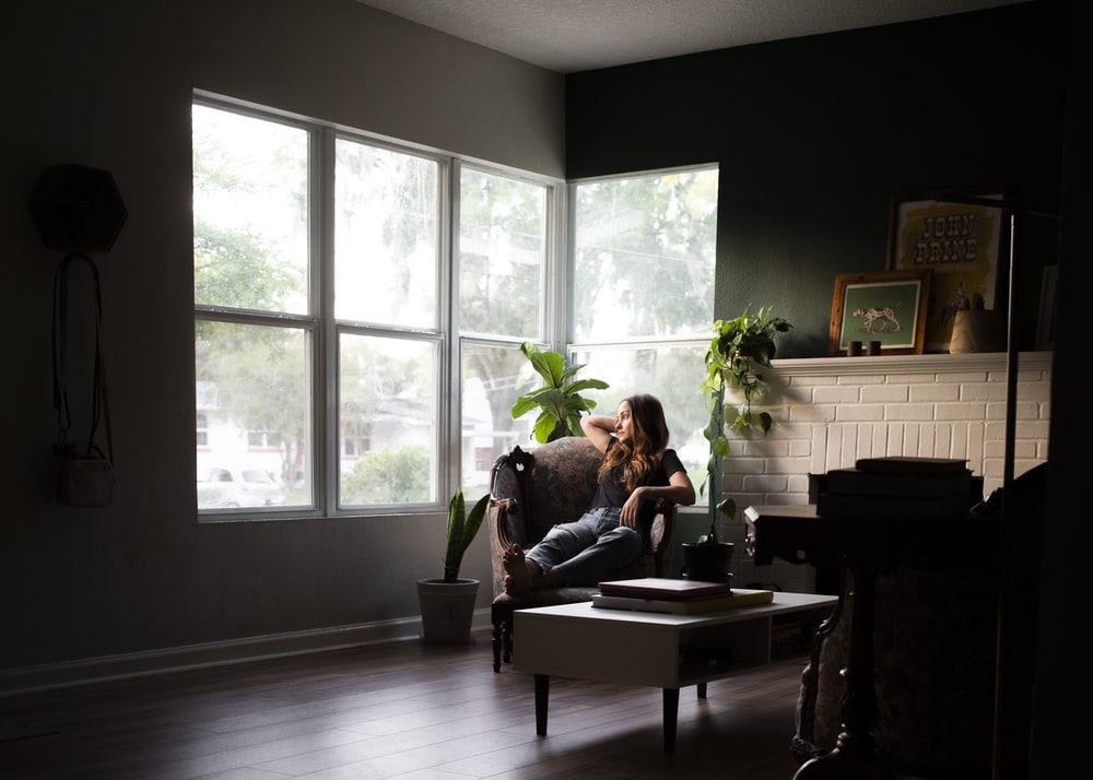 woman sitting on sofa chair near window