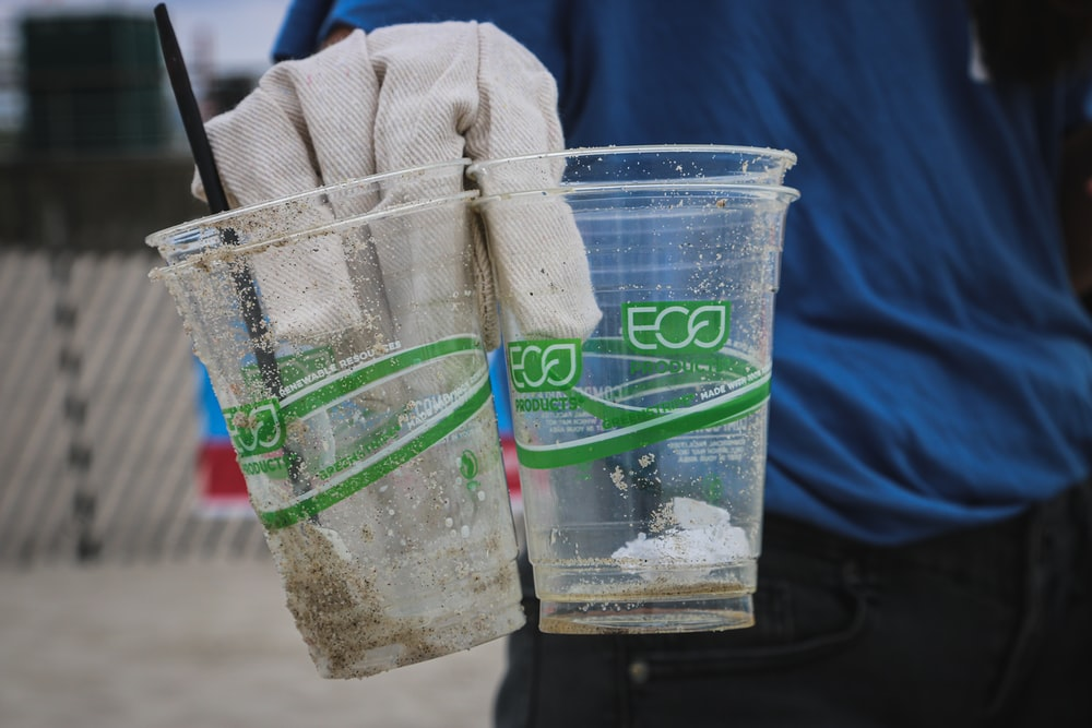 person holding two clear plastic disposable cups