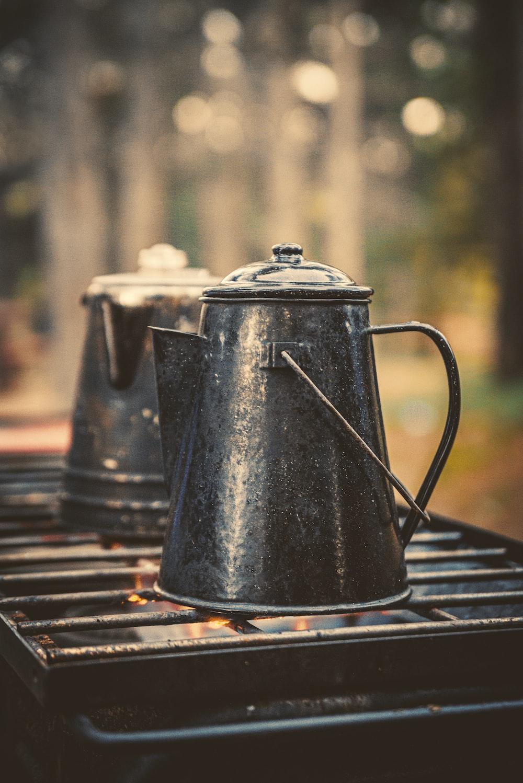 two grey metal kettles on black metal grill