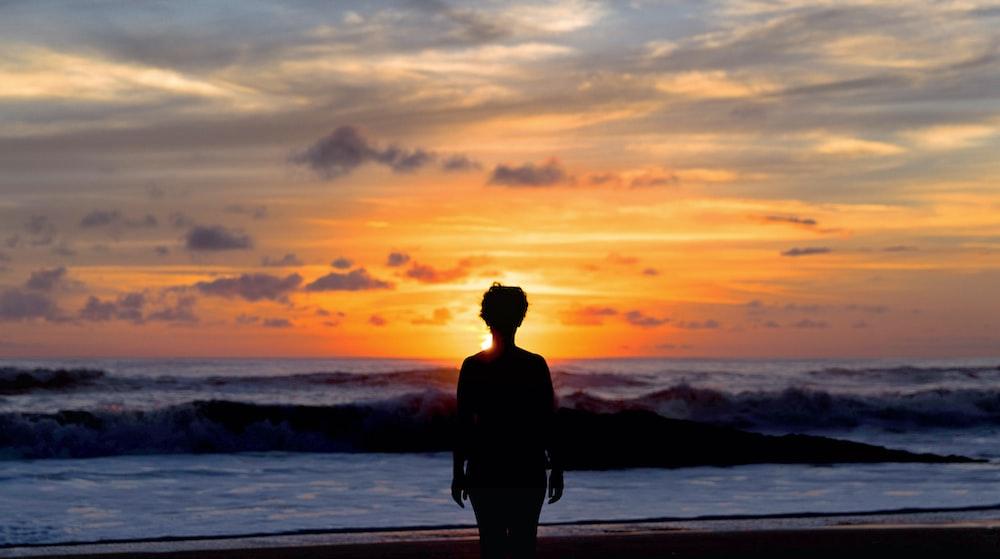 silhouette of woman standing near seashore