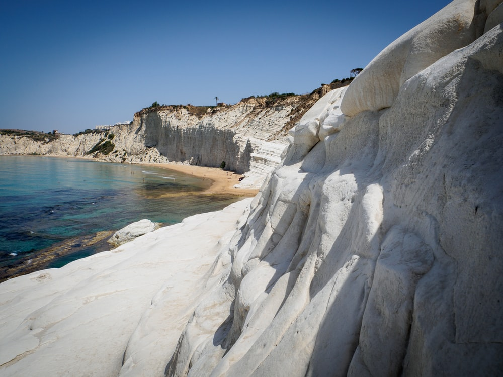 grey cliff near body of water
