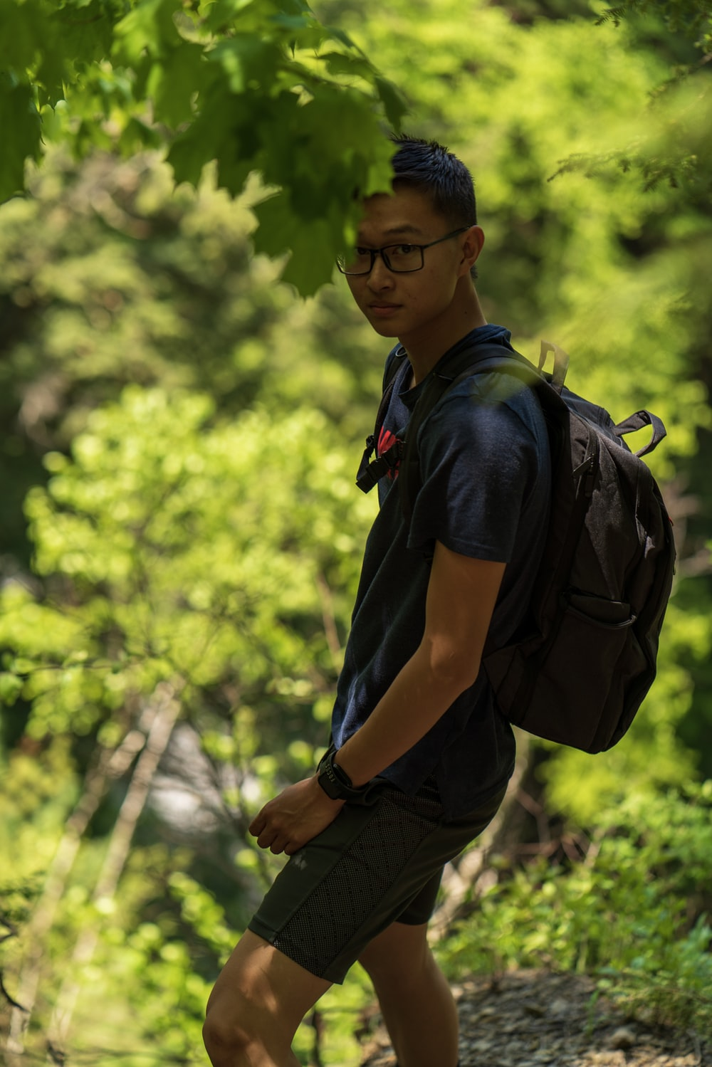 man in blue polo shirt carrying black backpack