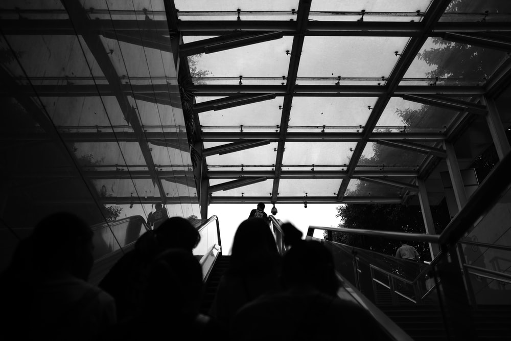 people on the stairs grayscale photo