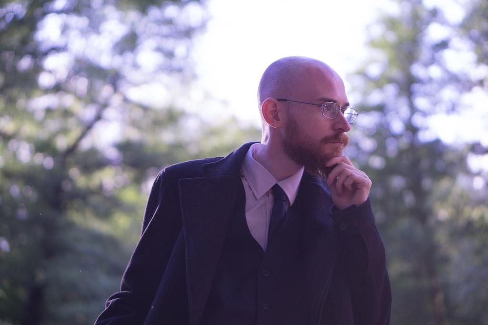 man wearing black coat holding his chin
