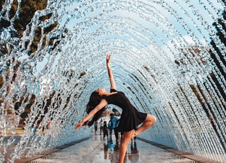 woman in black flare dress under water fountain