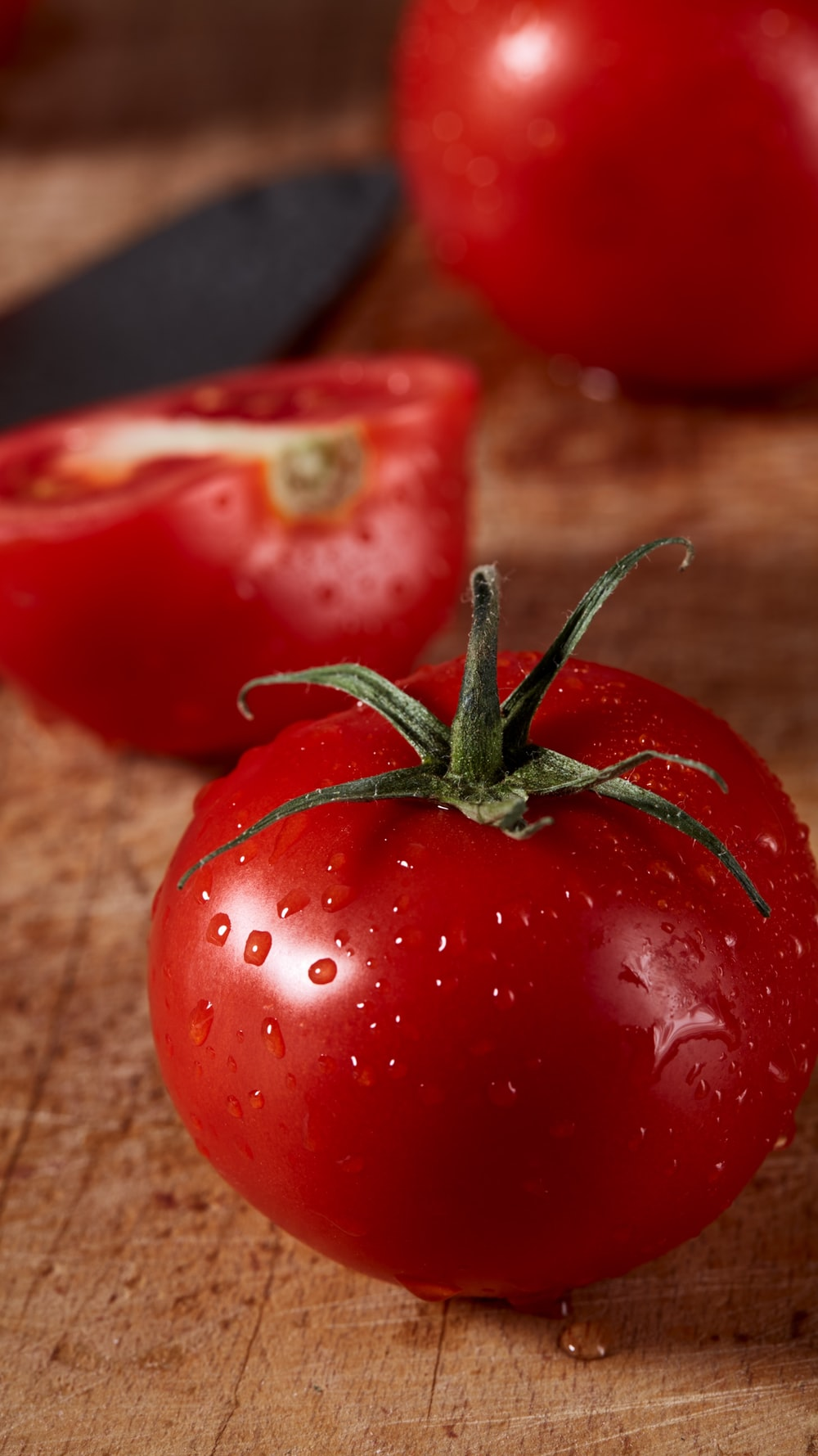 two red tomatoes beside sliced red tomato