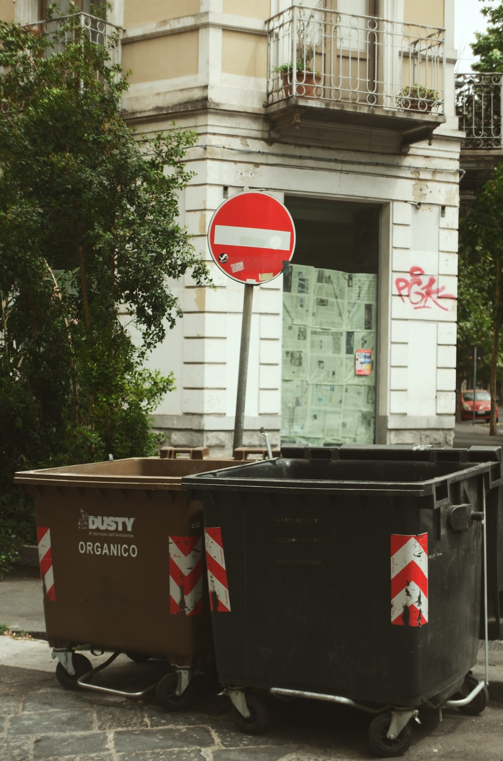 two opened dumpsters beside stop sign