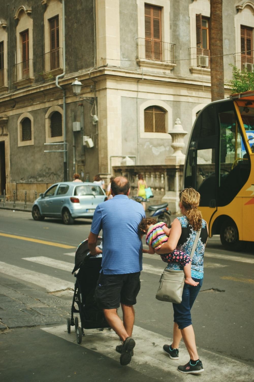 man wearing blue shirt pushing black stroller walking on street with woman carrying toddler during daytime