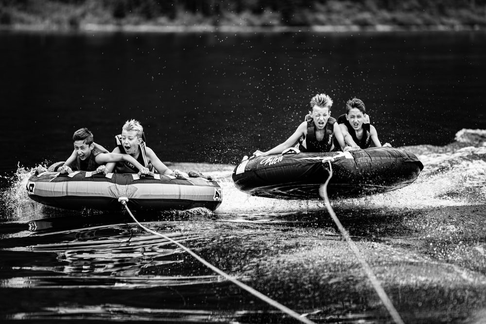 four children riding inflatable rafts pulled by motorized boat