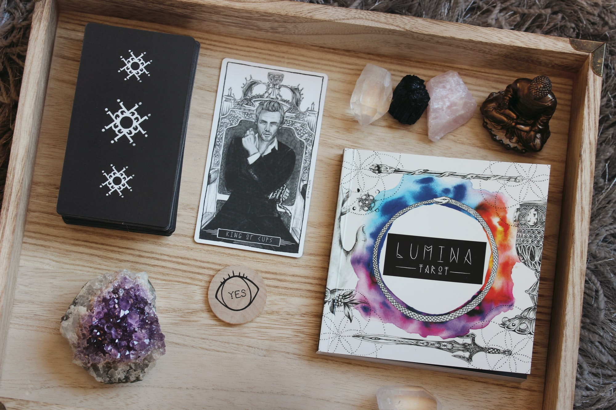The Lumina Tarot deck of cards and guidebook sit in a wooden tray with crystals and gemstones, Buddha statue and fortune telling wooden coin that reads YES. This is a makeshift altar for Eastern practices and tarot readings.